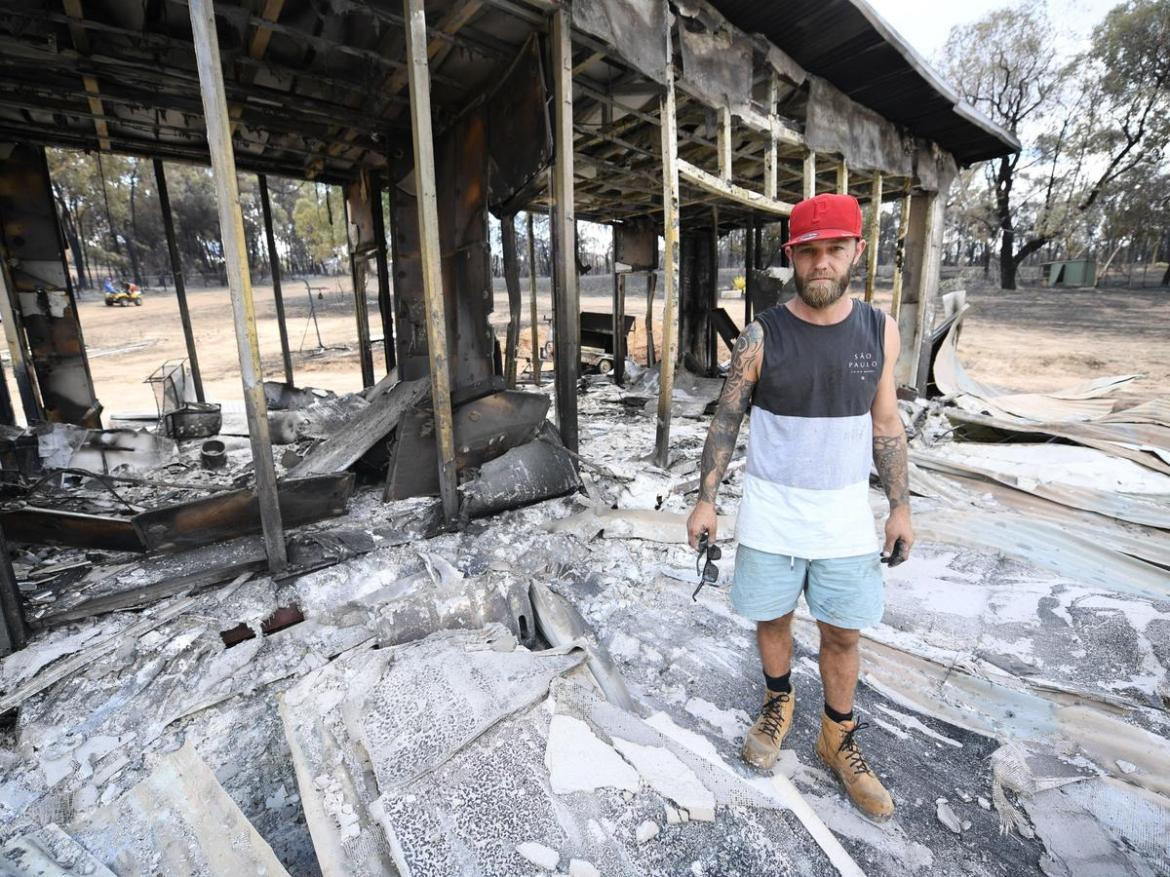 Lee Lyons goes through what's left of his belongings at his burnt out home.