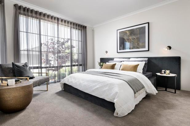 Positioned at the front of the house, the master bedroom is flooded with natural light and features a sleek design.