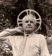 Adolfas Mekas holding a film reel behind his head like an angel halo