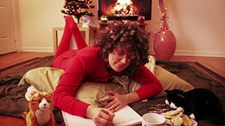 Woman wearing red pajamas writing a letter to Santa Claus