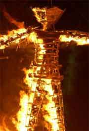 Burning Man sculpture on fire at night in the desert