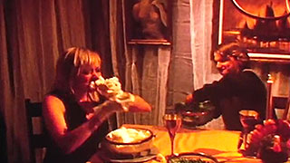 Woman shoving food in her face at the dinner table