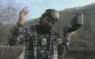 Bearded man dancing on a bridge while listening to a boombox