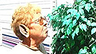 Older woman wearing an elf ear sniffing a plant