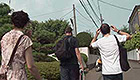 Three musicians walk down a Japanese street