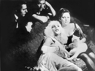 Mario Montez lies on a couch with a woman while Gerard Melanga and another man look on