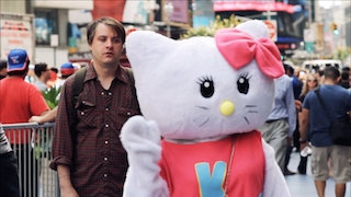 A man stares at giant female cat costume on a New York City street
