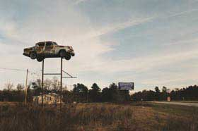 Car sits on top of a tall tower in an abandoned field