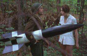 WWII soldier carrying a missile while talking to a pretty girl in a forest