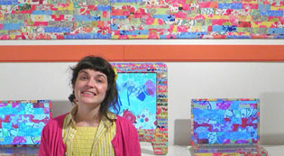 Jodie Mack standing in front of her colorful art installation