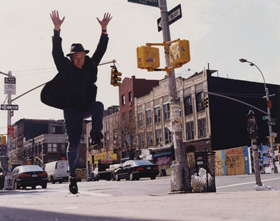 Jonas Mekas leaps into the air from a New York City sidewalk