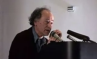 Jonas Mekas gives a lecture from a podium