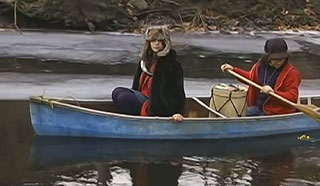 Man and a woman rowing a canoe down an icy river