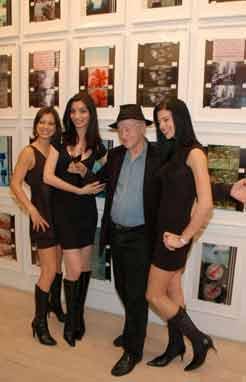 Jonas Mekas posing with a trio of pretty women