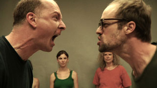 Two actors screaming at each other in a workshop