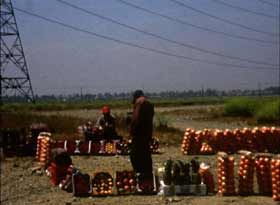 Man selling oranges while standing underneath powerlines