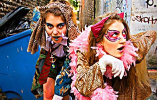 Two teenage girls dressed in colorful costumes running through an alley
