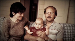 Mom and dad holding their baby while sitting on the porch