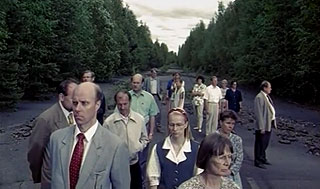 People standing on a dirt road in the middle of the woods
