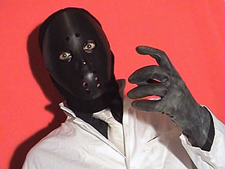 Menacing man wearing a black hockey mask in film still from The Slaves of Destructo