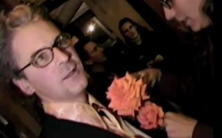 Filmmaker Craig Baldwin gets a flower placed in his lapel