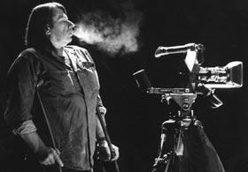 Filmmaker Stephen Dwoskin standing behind his camera
