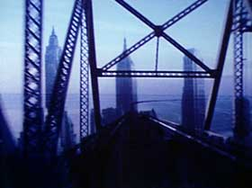 Film still from Bridges-Go-Round featuring a blue tinted bridge view of New York City