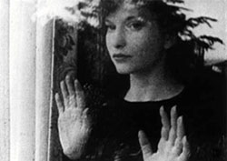 Film still from Meshes of the Afternoon featuring Maya Deren looking out a window