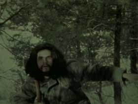 Film still of Dog Star Man featuring Stan Brakhage climbing a mountain
