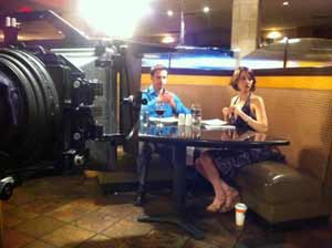 Movie shoot in which a couple eating dinner in a restaurant are being filmed