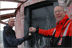 Rich Condit of the U.S. Coast Guard turns over the Thimble Shoal Lighthouse to Pete Jurewicz, left, near Fort Monroe, Va. Jurewiscz paid $65,000 at an auction for the lighthouse.