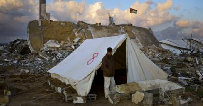 A Palestinian stands up outside a tent.