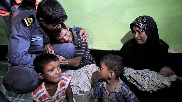 Mohammad Rafique, a Rohingya Muslim from Myanmar, center, begs a Bangladesh Coast Guard official not to send his family back to Myanmar.