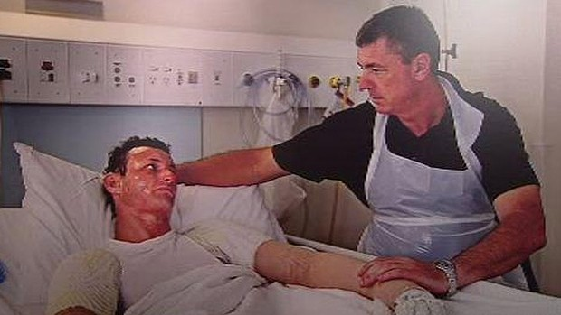 Police Commissioner Karl O'Callaghan comforts his son Russell during his stay in hospital after suffering injuries in a drug lab blast. Photo: Channel Ten.