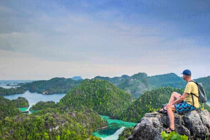 A Tourist Looking Out Over A Bay Of Islands From Harfat Mountain Spice Islands West Papua