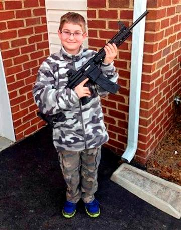 (AP Photo/Shawn Moore). This undated photo provided by Shawn Moore shows his son Josh, 11, holding a rifle his father gave him as a birthday present, at their home in Carneys Point, N.J.