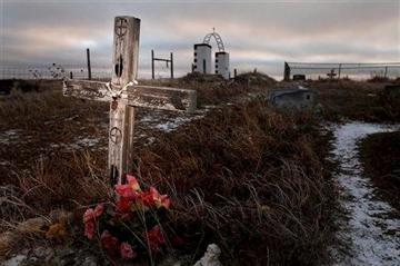 (AP Photo/Rapid City Journal, File). FILE - This Feb. 7, 2012 file photo shows a cross on a grave at the Wounded Knee National Historic landmark in South Dakota.