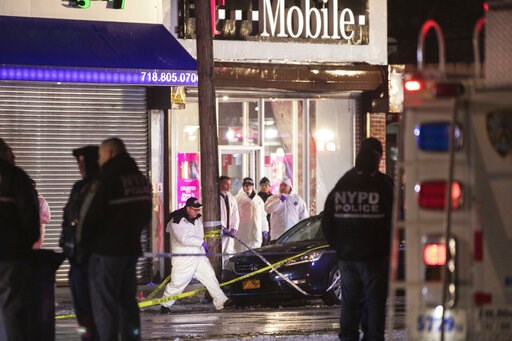 (AP Photo/Kevin Hagen). Investigators look over the area after a few New York City police officers were shot while responding to a robbery at a T-Mobile store in the Queens borough of New York on Tuesday, Feb. 12, 2019. An official said one of them was...