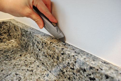 First I scored the clear silicone caulk by running a box cutter along the  top of the backsplash: