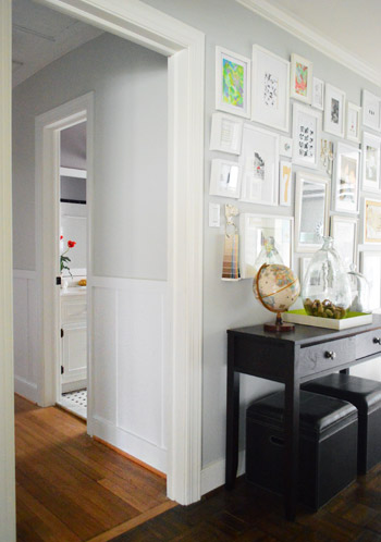 two adjoining hallways with different decor details, including frame gallery wall to wall and the other with board and batten molding