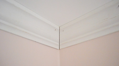 Corner of crown molding installed against ceiling with small seam at corner to be caulked