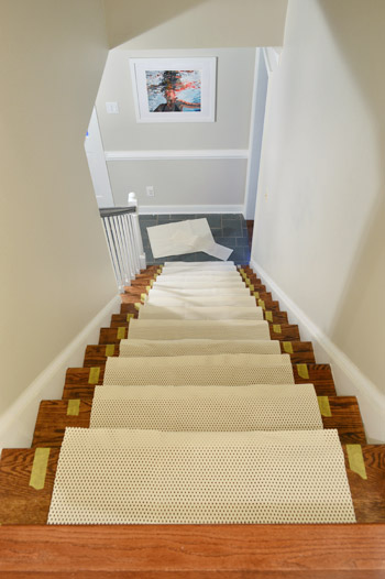 Sections Of Rug Pad Placed On Each Step Of Staircase Before Runner