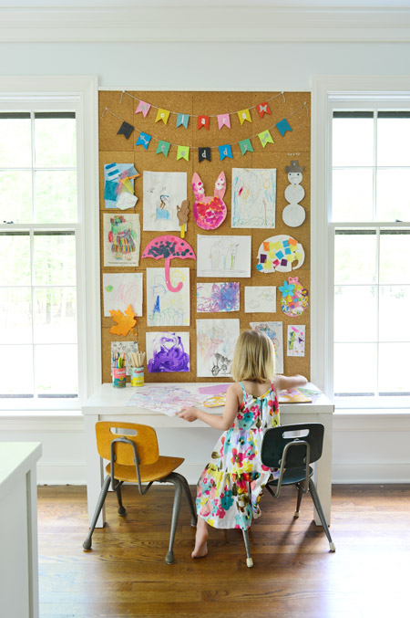 kids art displayed on large cork board wall in home office above kids art desk