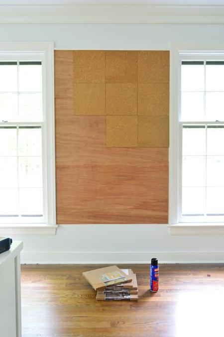 applying cork tiles to wall to create oversized cork board wall in kids art area