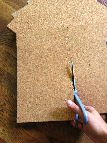 using scissors to cut cork tiles to fit to size on cork board wall