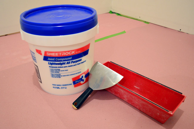 drywall mud or sheetrock join compound with spackle knife and mud pan