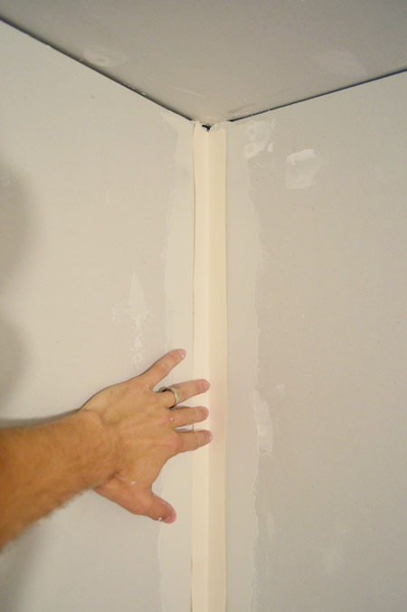 handing pressing drywall tape into corner layer of mud