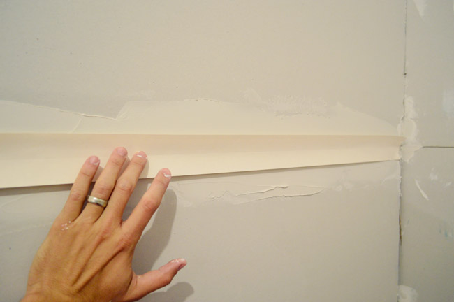 Hand Pushing Drywall Tape Into Bed Of Drywall Mud Along Seam