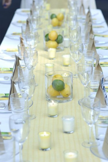 close up of backyard wedding reception table including yellow table runner and lemon lime centerpieces