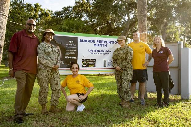 Sailors and civilians pose for a photo in recognition of Suicide Awareness Month.
